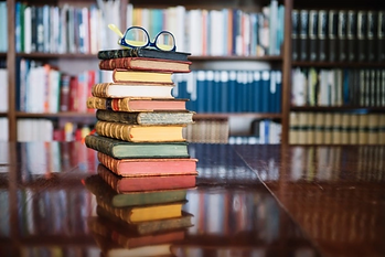 Library Books stacked with glasses.png