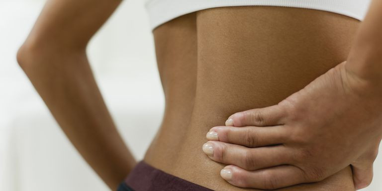 Women holding her back cause of pregnancy-related back pain