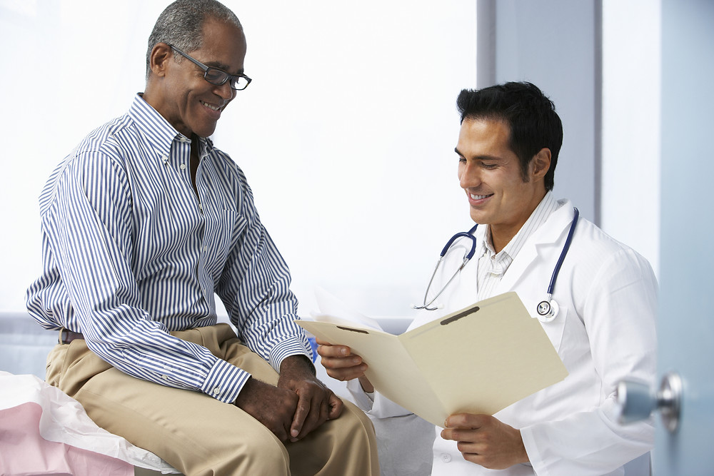 Male doctor reviewing chart with male patient