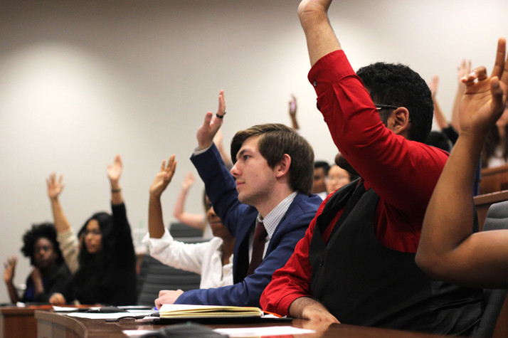 Liberal Arts senator Brandon Berens raises his hands with the majority of senate members in agreement of not going forth with an amendment to the resolution at hand during the general body meeting Sept. 26 in the Student Government Chambers. Berens recommended an amendment to include information about Social Security numbers for the resolution calling for the Office of International Studies to give more information to international students about obtaining proper identification cards.