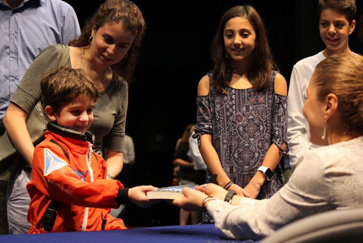 Dressed up in his astronaut gear, Mansfield resident Alexander Westbrook, 6, takes his book back after Anousheh Ansari, entrepreneur and first female private space explorer, signed her autograph Oct. 3 in Texas Hall. Westbrook said his favorite part of Ansari's speech at the Maverick Speakers Series was watching a video of Ansari floating inside of the International Space Station.