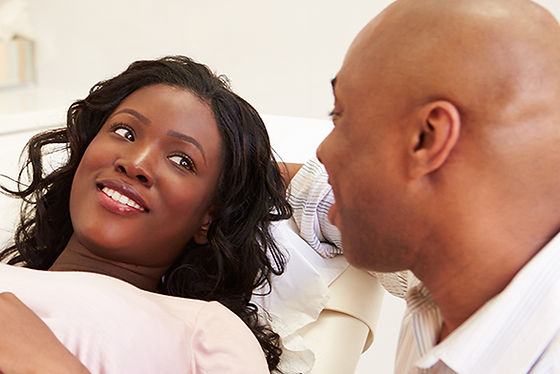 Black woman getting an ultrasound with her husband at her side