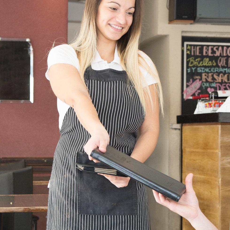 smiling-waitress-giving-menu-customer-re