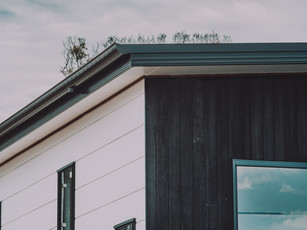 Corner of house showing contrast between white horizontal weatherboard and black vertical charred hardwood