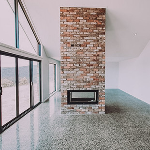 Polished concrete for solar passive thermal mass and recycled brick fireplace