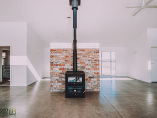 Burnished concrete floor and recycled brick fireplace for thermal mass