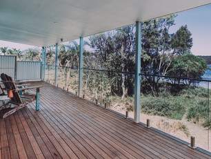 Ocean Views glass balcony railings, wooden deck facing the beach reserve