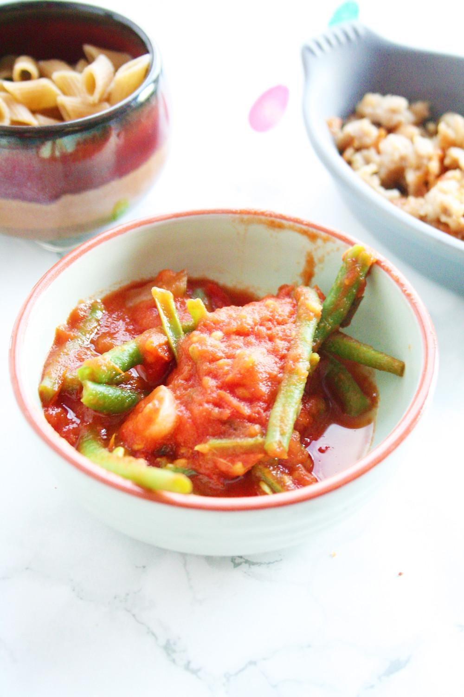 Pasta met pasta saus van tomaten, haricots verts, zilvervliesuitjes en kipgehakt