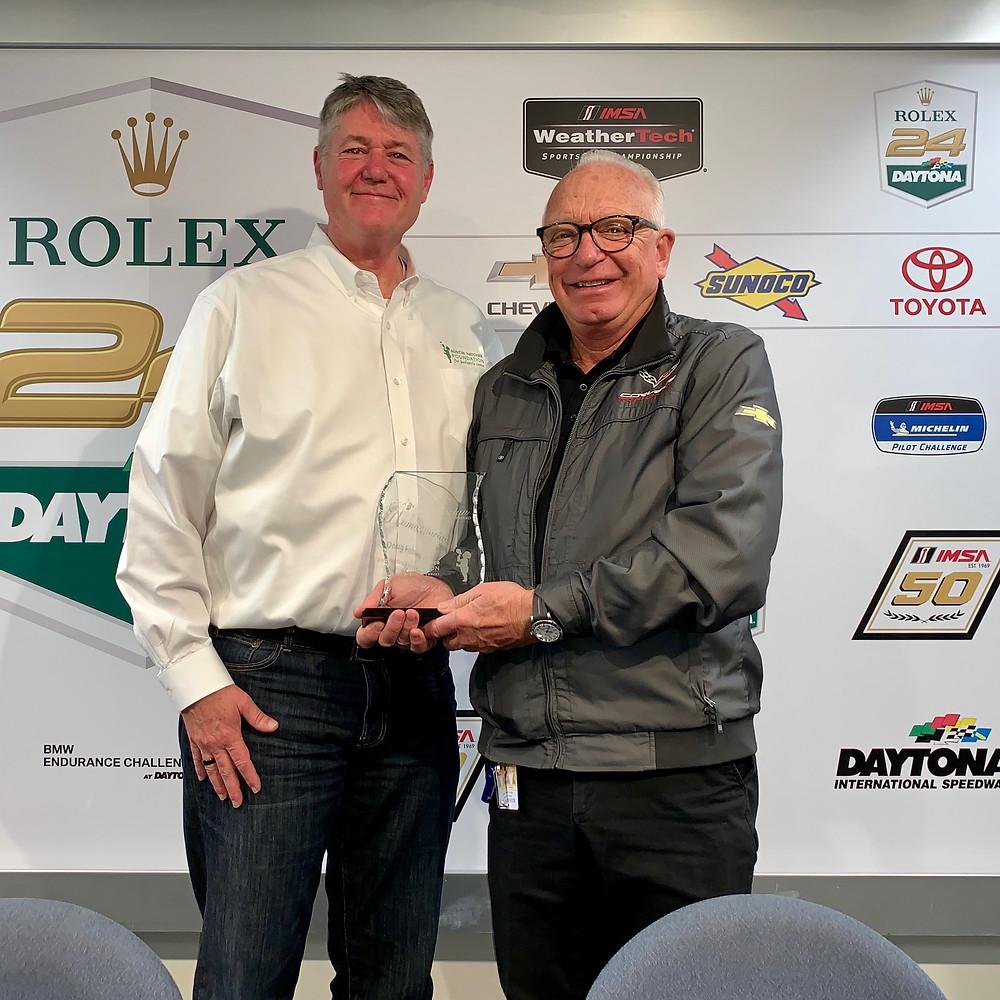 Austin Hatcher Foundation Chairman Jim Osborn presents award to Corvette Racing Program Manager Doug Fehan and General Motors President Mark Reuss.