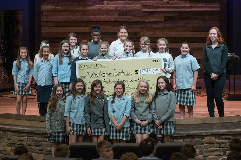 The winning class presents the check to Julia Sharp, Development Coordinator at the Austin Hatcher Foundation