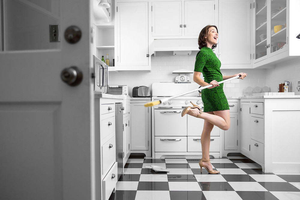 What does it mean to green clean - woman in a clean kitchen happy