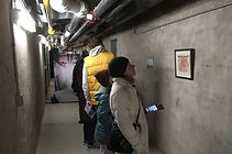 People standing in underground tunnel looking at artwork hanging along the walls
