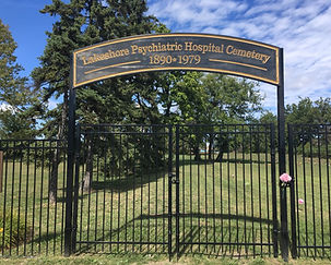 "Metal gated fence stands infront of grassed area with trees. Sign above entry reads: ""Lakeshore Psychiatric Hospital Cemetery 1890-1979"""