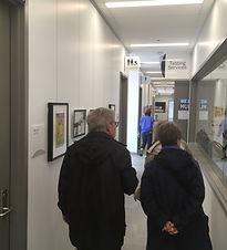 Man and woman walk down narrow hallway with artwork hanging along the walls