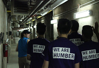 "Woman in blue shirt and baseball cap leads group of 4 people with shirts reading ""We Are Humber"" down a tunnel hallway"