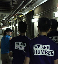 """Woman in blue shirt and baseball cap leads group of 4 people with shirts reading """"We Are Humber"""" down a tunnel hallway"""