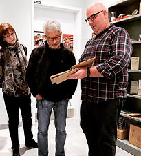 Man with glasses shows book to man and woman