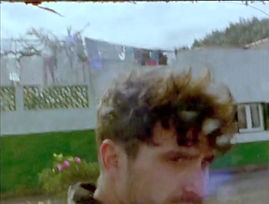 A screenshot featuring a profile of Alex from a VHS tape recording, with slightly distorted quality and colours. The top half of Alex's face is visible. He is turned to the right but he is looking into the camera. His hair is dark brown, short and very curly.