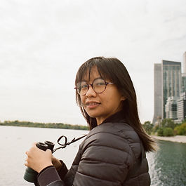 A photo of Carmina holding binoculars next to a large body of water with buildings in the distance. Through her large round glasses she is looking into the camera. Her long straight black hair rests on her dark puffer jacket.