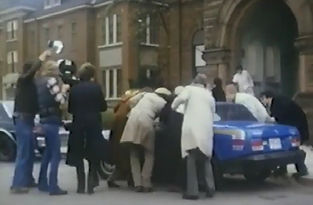Group gathers around a blue car in a still image from the film Phobia
