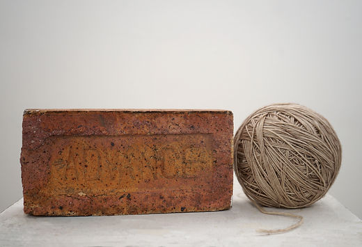 4kg and 8kg: A red brick with the word 'ADVANCE' imprinted onto its surface is placed  next to a ball of soft grey/beige yarn. The brick is deteriorating with age and is covered in black and white speckles. The ball of yarn is adjacent to the brick with the end of its string loose from the ball.