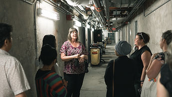 Woman with brown hair stands infront of a group of 7 people on tour in the tunnels underneath the Lakeshore campus