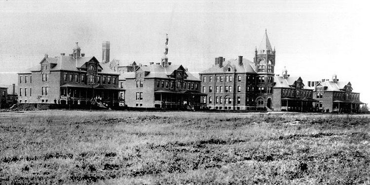 A Black and White landscape image of the former cottages of the Lakeshore Psychiatric Hospital Cottages. Five buildings pictured with an open grassy field in the foreground.