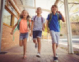 Happy school kids running in corridor at