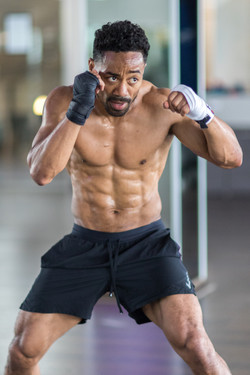 David Burnell boxing without a shirt wearing black nike shorts at Body Up Fitness Studios in Munich