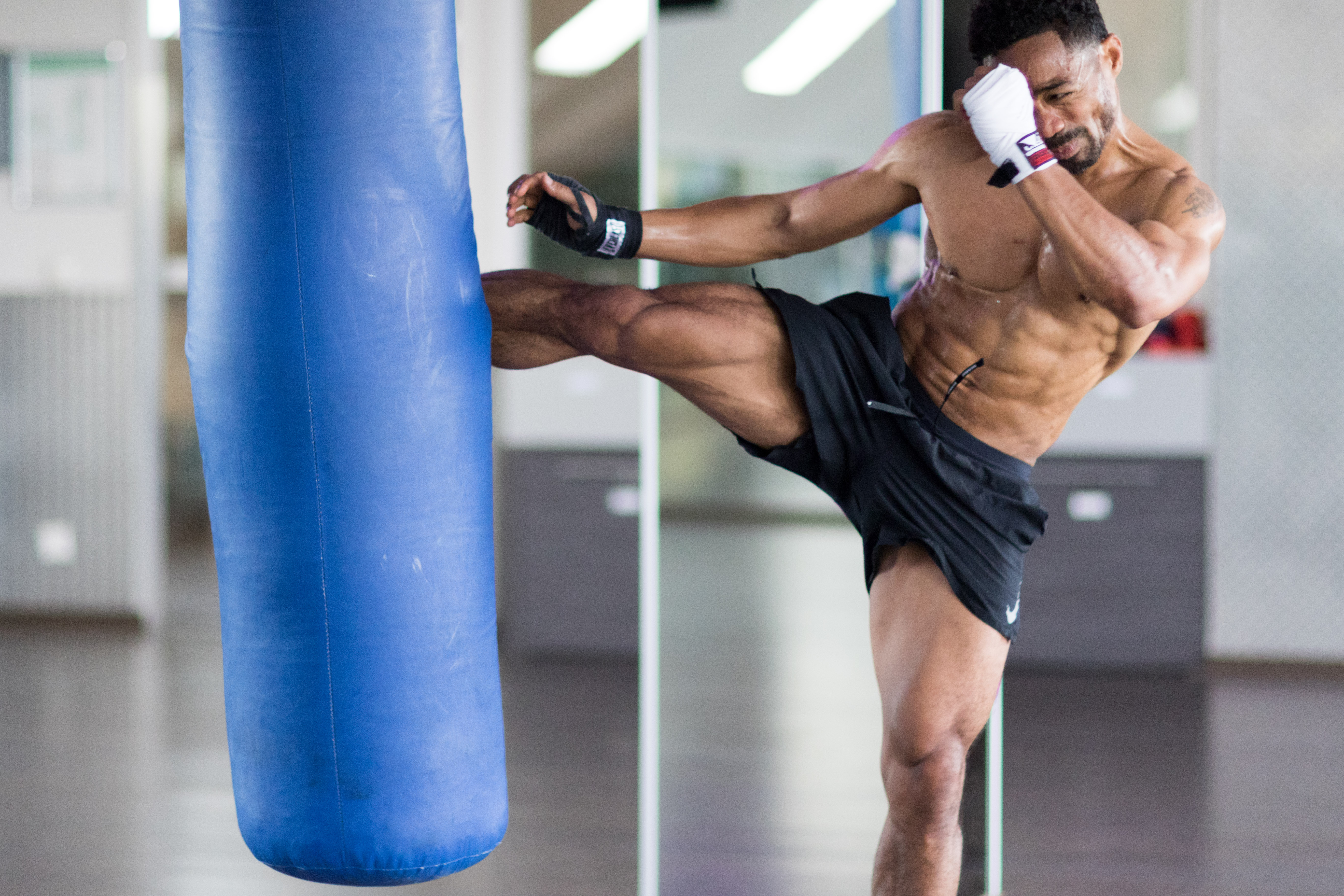 Light skin man kicking a blue punching bag without a shirt at Body up Giesing studios in Munich Germ