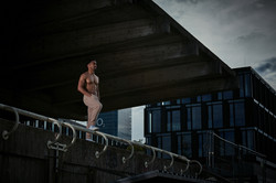David Burnell standing on the edge of the abandoned railroad station with a beige jogging pants at t