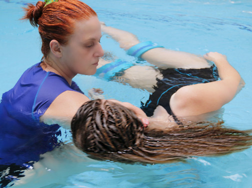 Instructor and practitioner Anat Juran is giving a young woman a Healing Dance aquatic bodywork water therapy session