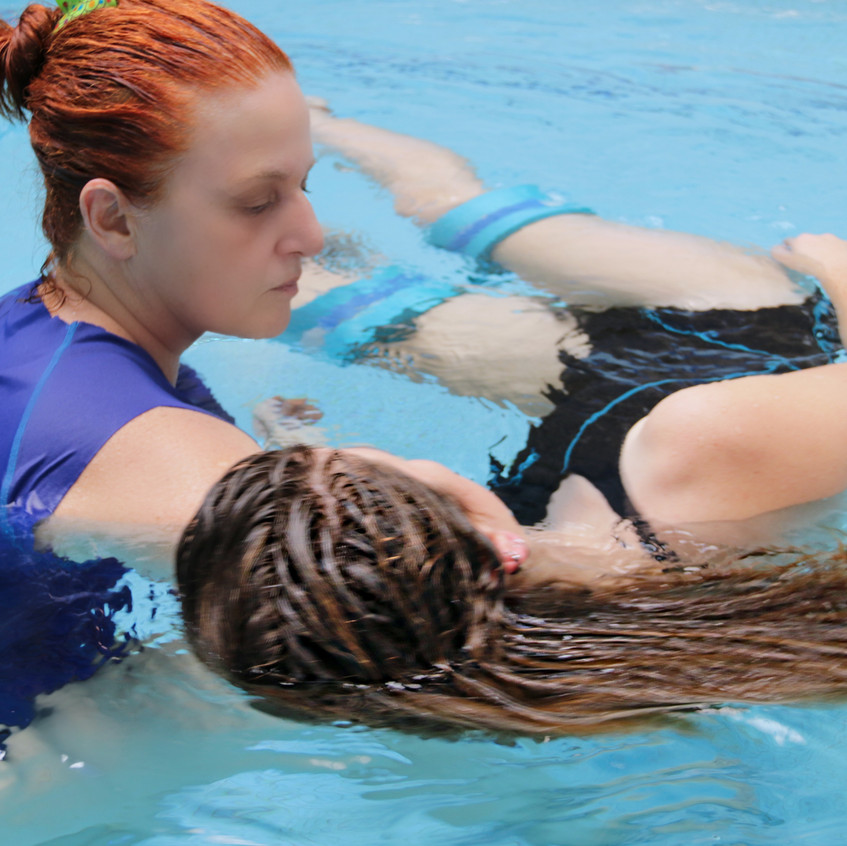 a woman is holding another woman in a pool during an aquatic therapy session