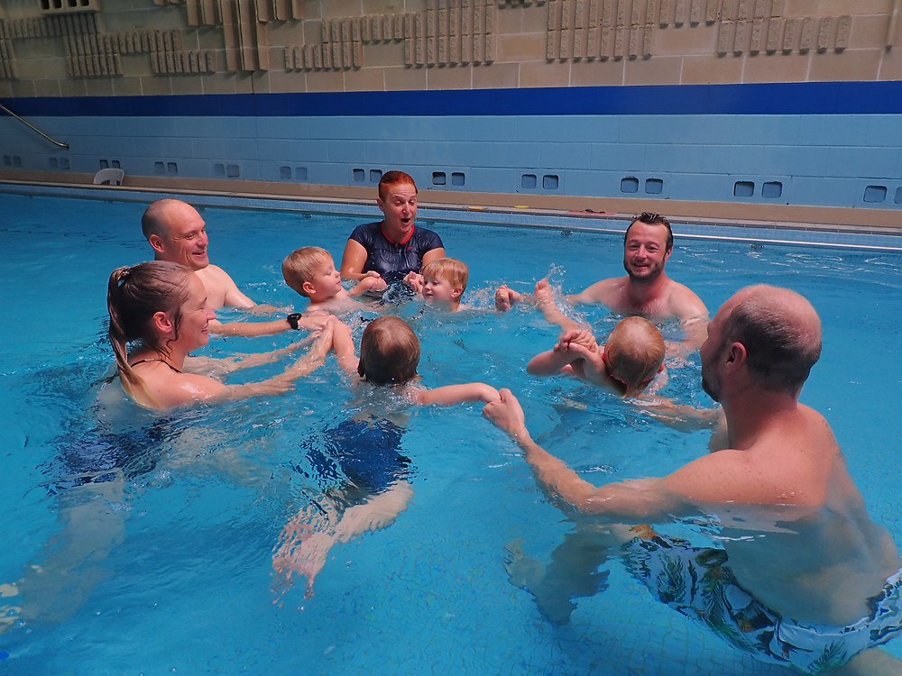 Parents and toddlers playing and smiling during their swimming class
