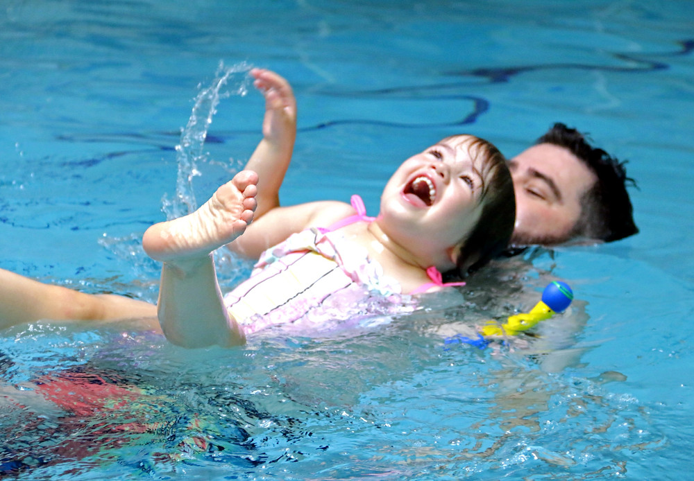 Laughing girl wearing a pink bathing suit is lying back in a swimming pool splashing her feet and hands while a man supports her in the water.