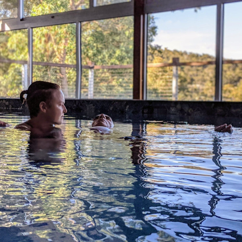 a woman is holding a man in a pool with view of trees during a watsu aquatic bodywork hydrotherapy session