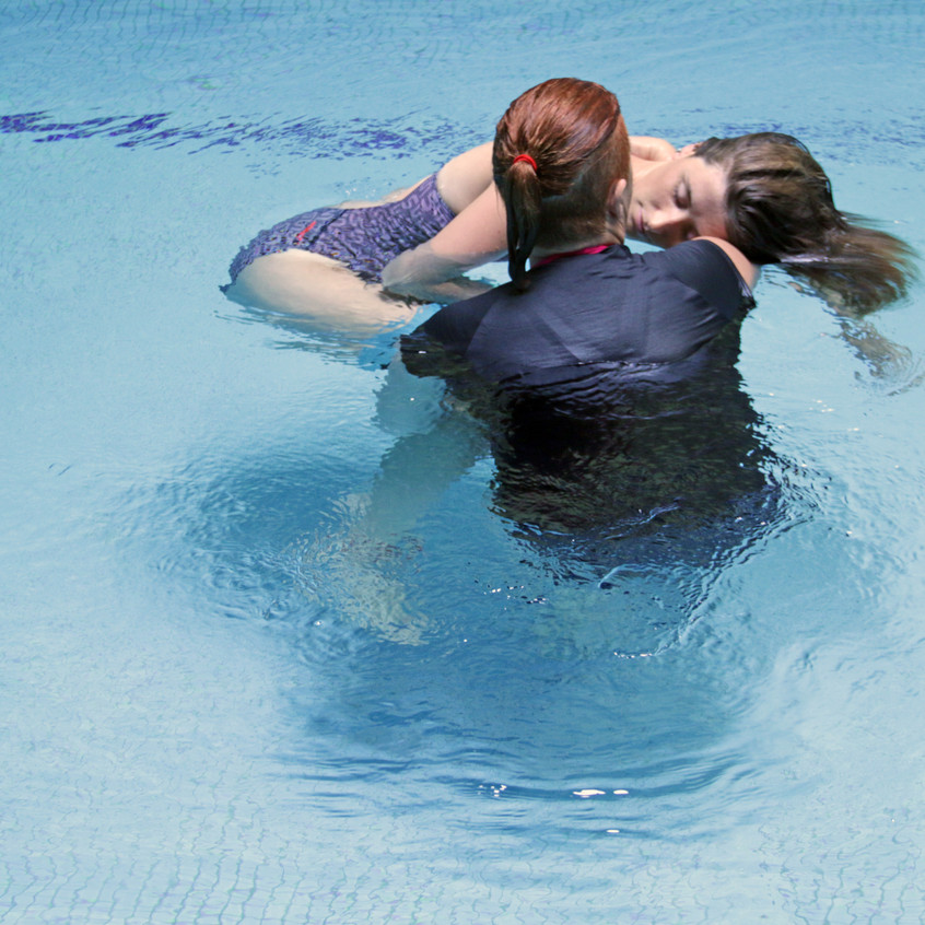 a woman is holding a young woman client in the pool water during a water therapy sesison