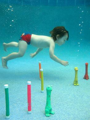 Aquanat kid underwater bringing toys in