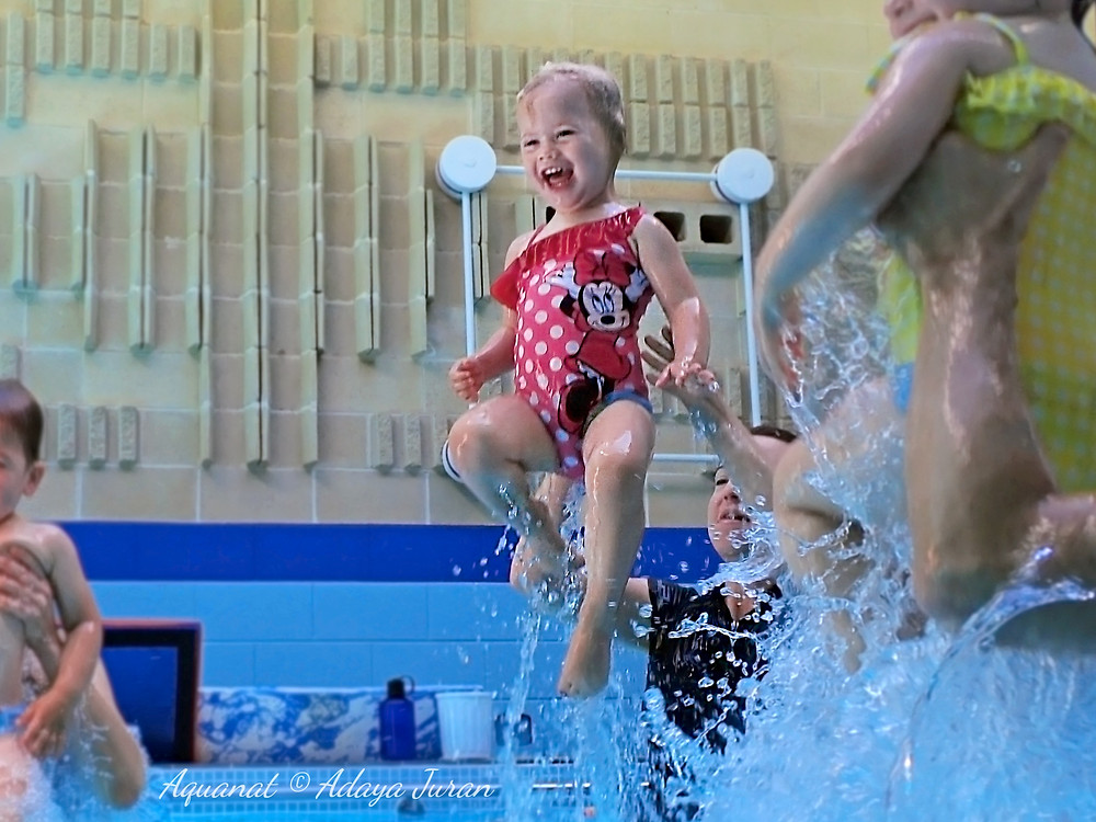 Toddler in a pool wearing a red Minnie Mouse swimsuit smiling as she is thrown into the air by a swimming instructor during a children's swimming lesson