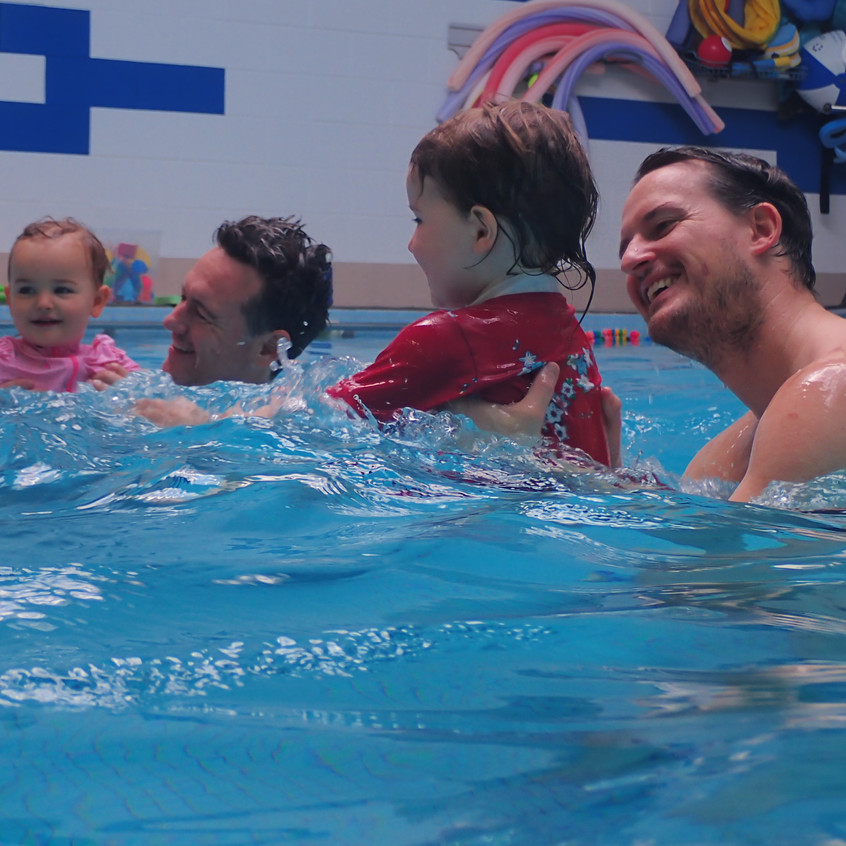 Dads holding their smiling daughters in the pool during their group baby swim lessons