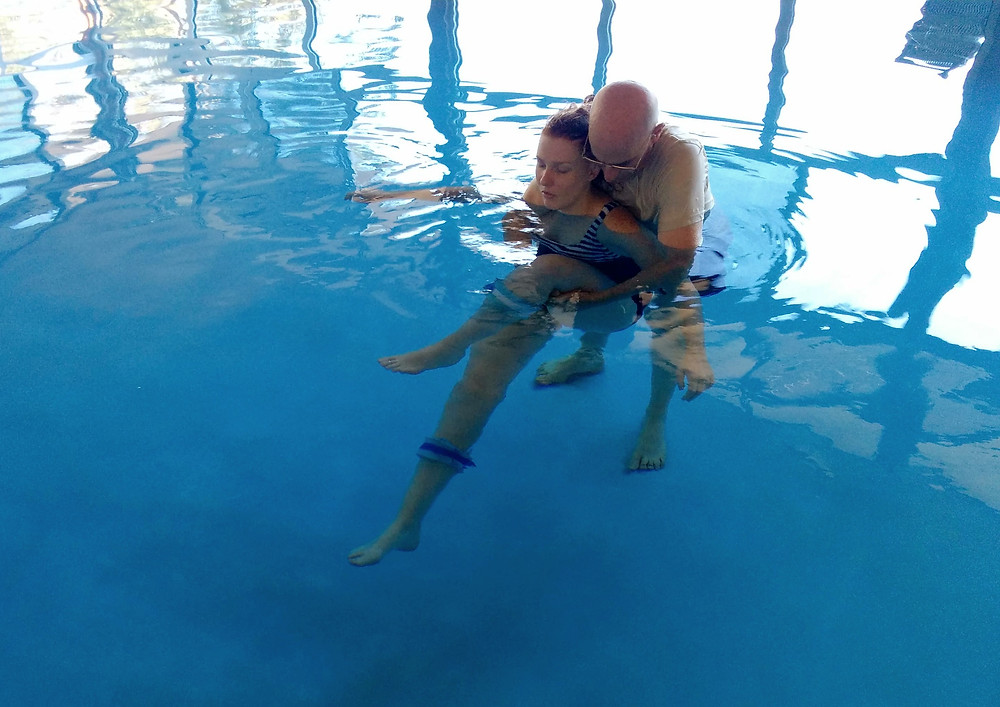 A bald man is embracing a young woman with her eyes closed in a pool facing away from him during a practice Watsu session