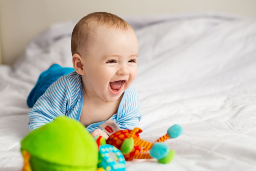 A smiling baby is laying on his stomach on a bed next to colourful toys