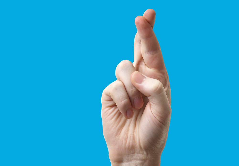 One hand with crossed fingers on a light blue background