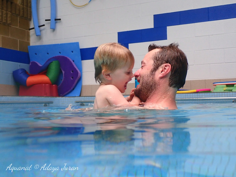 baby floating in the pool held by swimming teacher