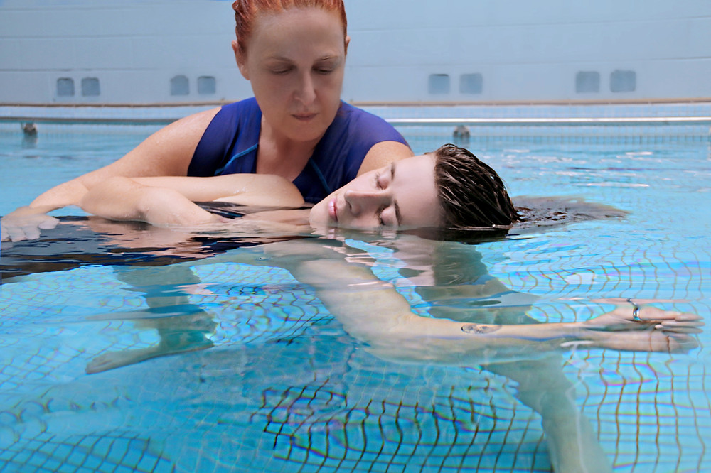 Watsu practitioner Anat Juran taking a low stance in the water while she holds a woman with her arm extended and floating during a Watsu session