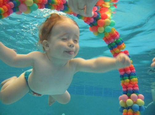 Cute funny baby is diving underwater through colourful hoop and sticking tongue out while in a swimming lesson