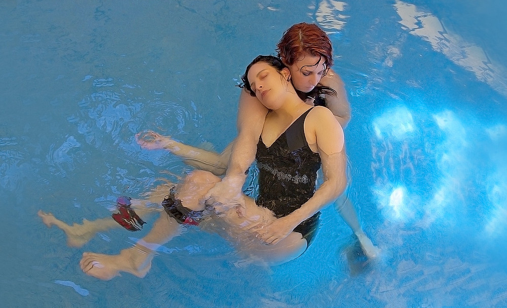 View from above of a woman in a black swimsuit receiving a Watsu session from Watsu instructor Anat Juran in bright blue water
