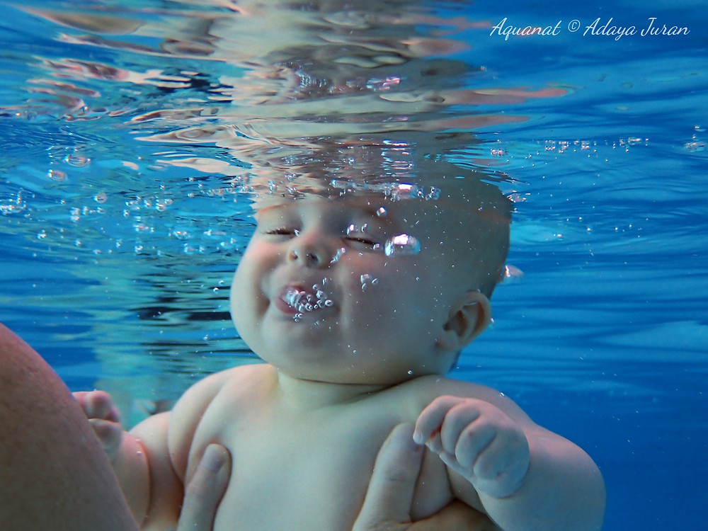 A baby with their eyes closed blowing bubbles under water as they are held by a woman's hands