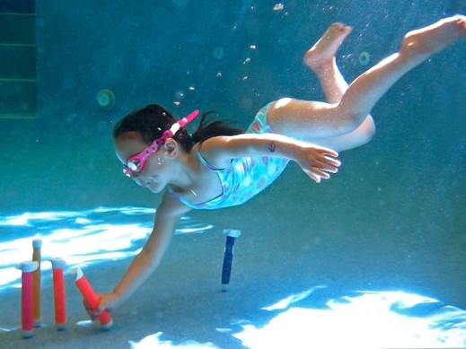 Aquanat girl underwater diving for toys