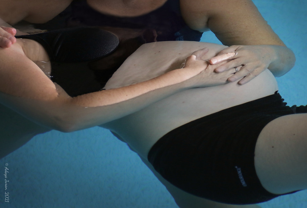 close up of hands gently touching pregnant belly while being floated in a pool